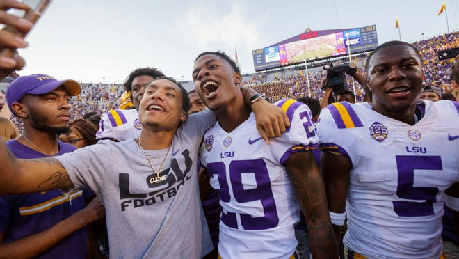LSU's Greedy Williams (29) poses for a selfie as fans rush the field  after the Tigers 36-16 win over Georgia in an NCAA college football in Baton Rouge, La., Saturday, Oct. 13, 2018. (AP Photo/Matthew Hinton)