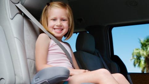 Girl riding in booster seat.