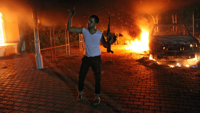 A man waves his rifle as buildings and cars are engulfed in flames inside the U.S. consulate compound in Benghazi, Libya,  on Sept. 11, 2012.
