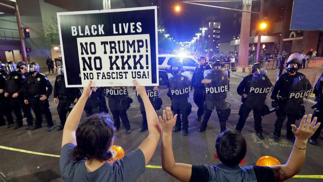 Protesters raise their hands after Phoenix police used gas outside the Phoenix Convention Center on Aug. 22, 2017, in Phoenix. Protests were held against President Donald Trump as he hosted a rally inside the convention center.