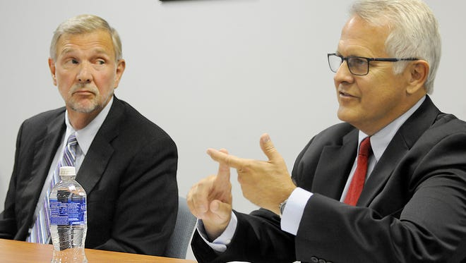 Ron Abrams listens to Mayor Tim Theaker make a point Tuesday as the two debated at the News Journal.