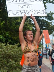 File photo: Ashlee Dawson, an Ocean City Boardwalk performer, holds a sign to attract signatures during a protest of new street performer regulations outside of Ocean City City Hall.
