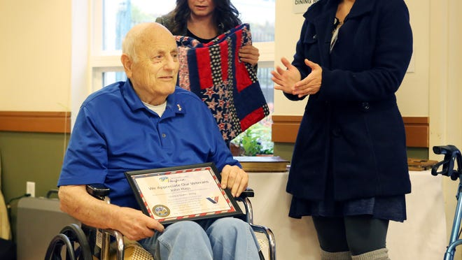 World War II veteran John Hays (center) is honored by Willamette Valley Hospice social worker Kimberly Fleck (back) and nurse Ana Cabrales during a pinning ceremony on Thursday, Nov. 13, 2014, at Friendsview Retirement Community in Newberg.