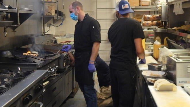 Josh Ward, sous-chef at Outriggers Tiki Bar and Grille in New Smyrna Beach, at left, works the grill with Christopher Morales, in hat. The restaurant is among businesses in Volusia and Flagler counties who may not have been able to continue without a PPP loan.