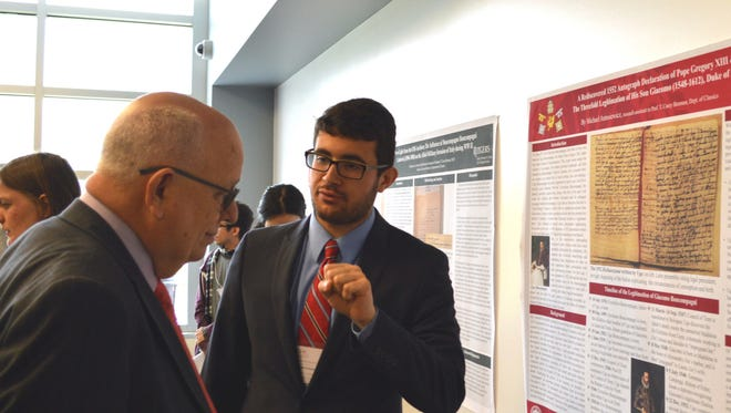 Michael Antosiewicz (right) chats with Barry Qualls, vice president of undergraduate education and professor emeritus of English, during a past undergraduate research symposium.