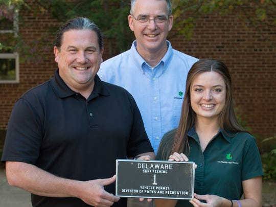 In an archived photo, Aaron Dunphy, left with lowdigittags.com, Greg J. Abbott, manager, Administration & Support Section with DNREC and Abbey Shepherd, marketing assistant with DNREC, hold Delaware Surf Tag 1.