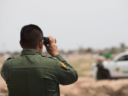 A U.S. Border Patrol agent looks at U.S. Vice President