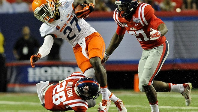 Mississippi defensive back Mike Hilton (28) and defensive end Marquis Haynes (27) tackle Boise State running back Jay Ajayi (27) during the first half of an NCAA college football game in Atlanta, Thursday, Aug. 28, 2014. (AP Photo/The Daily Mississippian, Thomas Graning)