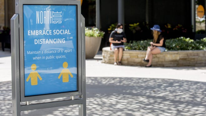 A sign at Domain Northside in May encourages social distancing among shoppers. Many employers in the Austin area have been adding workers to their payrolls in the last few months, after the coronavirus pandemic triggered massive layoffs and furloughs earlier this year.