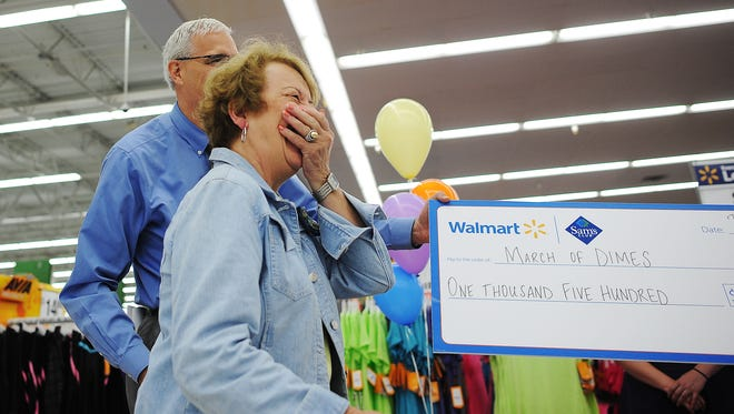 Carol Flynn reacts as she realizes that Walmart is making a $1,500 donation on her behalf during a thank you event on Thursday westside Sioux Falls Walmart.