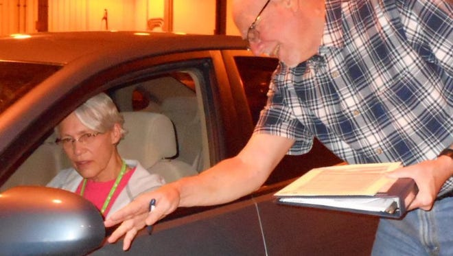 A CarFit volunteer reviews checklist with driver to ensure safe driving techniques.