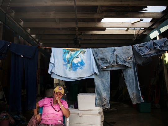 """Crystal Holler waits for her clothes to dry in the garage of her neighbor's home in Chokoloskee on Wednesday, September 13, 2017, three days after Hurricane Irma. """"All of my clothes came flying out of the house,"""" said Holler. She returned home to find her clothing covered in mud in her yard."""