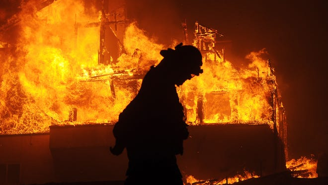 A fireman walks past a home engulfed by fire at North Fir and Buena Vista streets in Ventura on Dec. 6.
