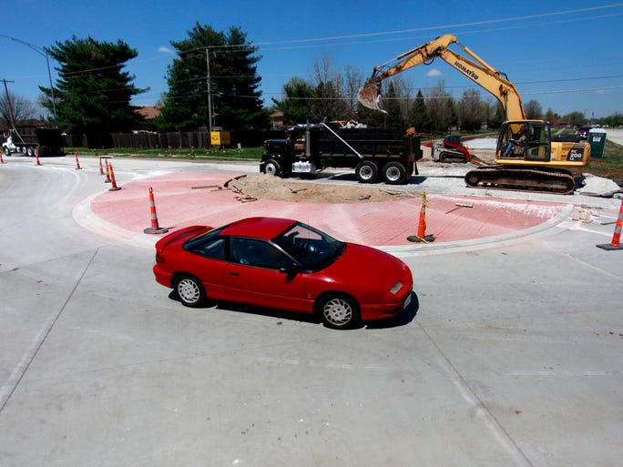 A car drives east on Walnut Lawn Street on Tuesday as a construction crew works to make a roundabout at the intersection with South Maryland Avenue.