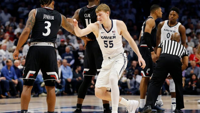 Xavier Musketeers guard J.P. Macura (55) fist bumps with the Bearcats starting five before the first half of the 85th Annual Crosstown Shootout game between the Xavier Musketeers and the Cincinnati Bearcats at the Cintas Center in Cincinnati on Saturday, Dec. 2, 2017. At halftime the Musketeers led 43-30.