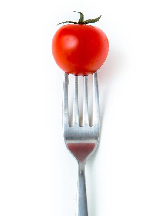 little tomato on fork