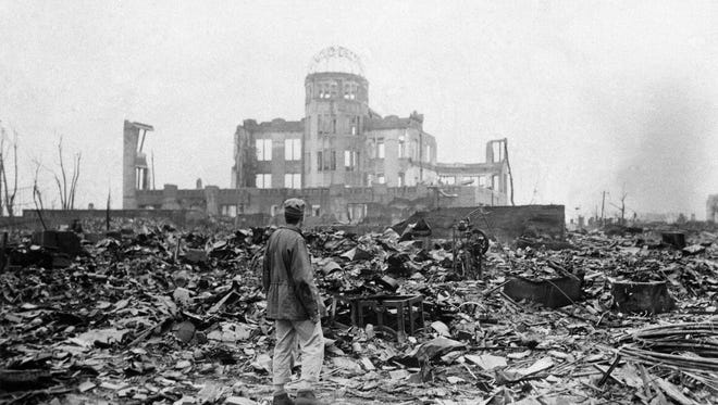 In this Sept. 8, 1945 file photo, an allied correspondent stands in the rubble in front of the shell of a building that once was a movie theater in Hiroshima, Japan, a month after the first atomic bomb ever used in warfare was dropped by the U.S. on Monday, Aug. 6, 1945. In a moment seven decades in the making, President Barack Obama this month will become the first sitting American president to visit Hiroshima.