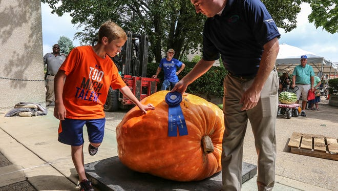 Maxwell Daley, 12, is congratulated by Kentucky Agriculture Commissioner Ryan Quarles at the Kentucky State Fair.  Daley's pumpkin weighed in at 582.5 lbs. August 19, 2016