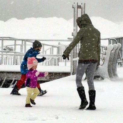 Stephanie Sherwood plays with her children on the snow