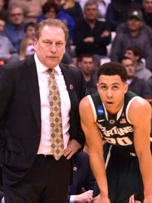 Travis Trice consults with Tom Izzo on the sideline as MSU plays Oklahoma.