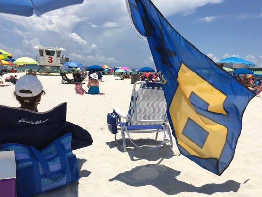 Jan Corley of Pensacola Beach flies a No. 6 flag as she waits to watch the Blue Angels.