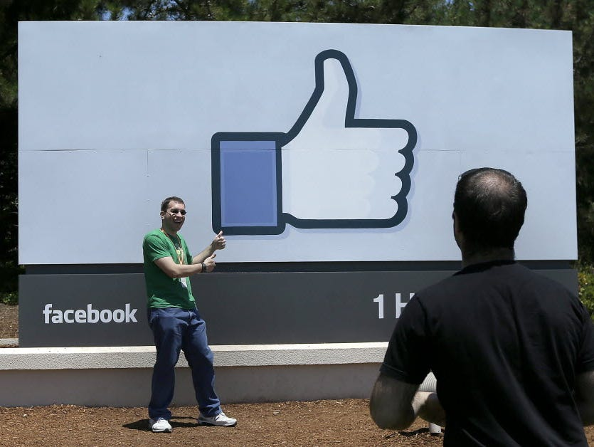 A man poses in front of the Facebook sign on the company's campus in Menlo Park, Calif.