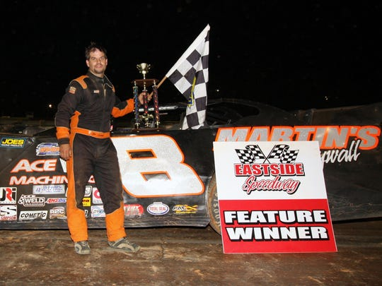 Joey Leavell poses with the trophy and the checkered flag he received for winning one of the two Late-Model features at Eastside Speedway on Saturday, Sept. 3, 2016.
