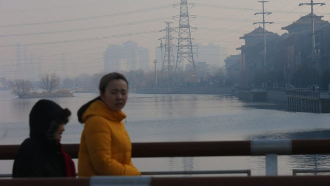 People walk on a bridge during a haze day in Beijing on Jan. 14, 2018. Beijing issued an orange alert for smog, its first major alert this winter.