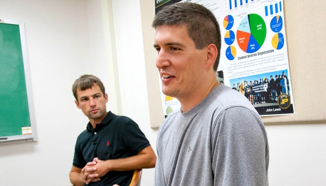 Purdue University doctorate student Will McGee, right, speaks about his time serving with the Marines in Iraq at the Veterans Success Center in West Lafayette, Ind., on Aug. 22, 2013.