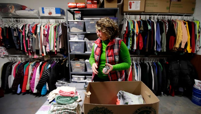 Shelley Aaholm, a Spanish teacher at Neenah High School, organizes donated clothing while restocking items for Neenah High School's Orbit program. The program was started in 2013 to help students in need.