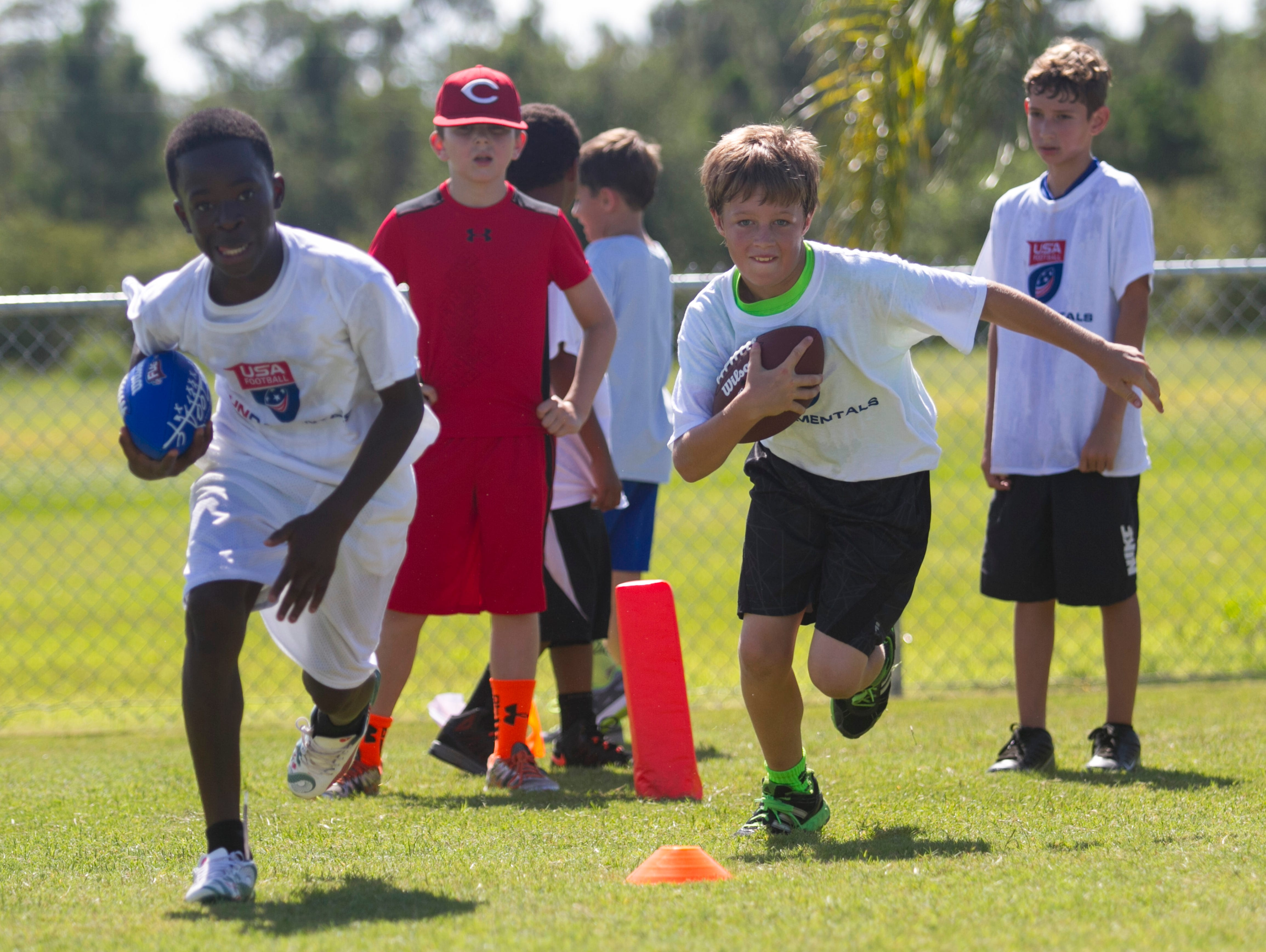 A group runs drills at a free youth football camp at McGregor Baptist Church run by Nate Allen of the Oakland Raiders on Saturday.