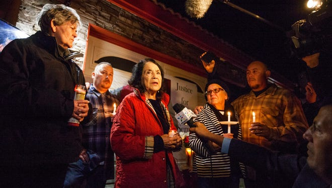 In this photo provided by The Bakersfield Californian, activist Dolores Huerta, center, speaks at a candlelight vigil for Francisco Serna, 73, Tuesday, Dec. 13, 2016, in Bakersfield, Calif. From right are Serna's son Frank Serna, wife Rubia Serna and son Roy Serna. Serna was shot and killed by a Bakersfield, Calif., police officer near his home early Monday. Police Chief Lyle Martin said Tuesday that the unarmed Serna refused to take his hand out of his pocket when he was shot by an officer who thought he had a gun. Serna's family said he suffers from dementia and he often took walks in the evening.