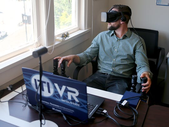 PSNS lifting and handling training supervisor Dylan DeMers operates a virtual reality system that runs a crane operation training program.