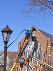 Brick masons remove loose bricks from the facade of St. Paul's Episcopal Church in 2017.