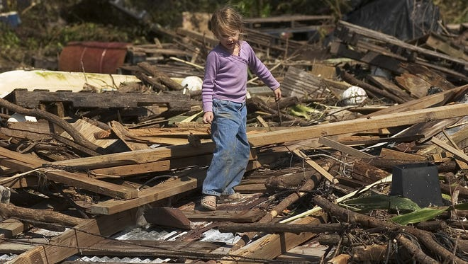 Wendy Lynn Raffield, 5, plays on a debris pile of stone crab traps and a washed up dock in Chokoloskee.  Raffield's home was flooded by Hurricane Wilma.