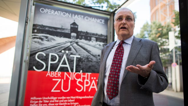 "Efraim Zuroff, the top Nazi-hunter of Simon Wiesenthal Center, stands in front of a sign reading, ""Operation last chance - late but not too late,"" displayed in Berlin on July 23, 2013."