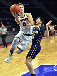 Milford's Mitch Appleton (4) goes in for the layup
