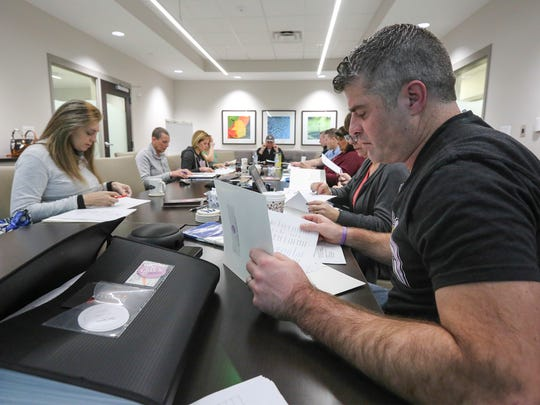Bart Conley, right, looks over paperwork during a Jill's Wish Foundation board meeting.  Bart has struggled as he's been trying to move forward after her death almost a year ago. January 14, 2017