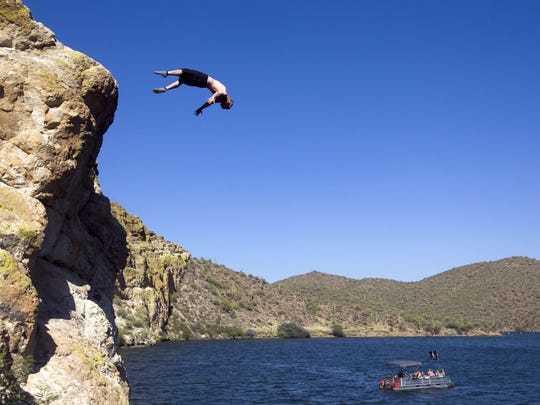 A visitor does a back flip off a cliff into Saguaro