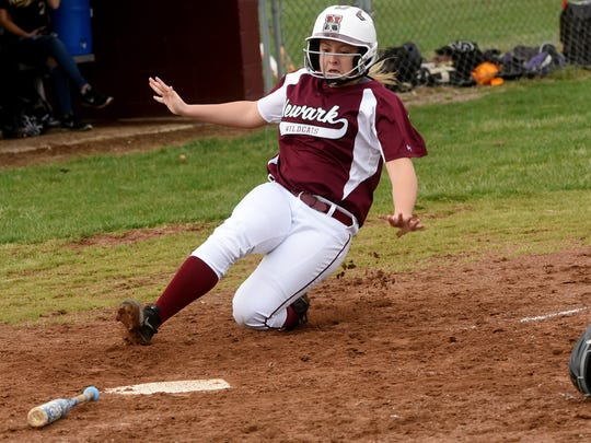 Newark's Logan Bannworth slides in to home plate to score the tying run against Watkins Memorial. The game was suspended just before the first pitch of the top of the seventh inning because of lightning and later heavy rain. The game will not be finished unless the two teams can work a second game into the schedule later in the season.