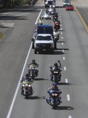 A group of 50 motorcyclists escort a truck on Interstate 5 that hauled a special cart to be used for dead soldiers arriving in their caskets at San Francisco airport.