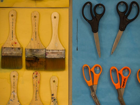 Pairs of scissors and paint brushes hang from thumbtacks in John Gentry's visual arts classroom at Owensville Community School.