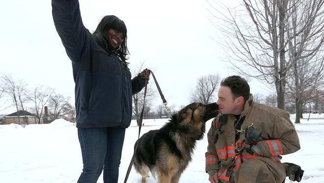 Firefighter Michael Paveljack, right, gets a kiss from Mack the dog he rescued  from a sink hole in Buffalo,  N.Y. Sunday Feb. 2, 2014.