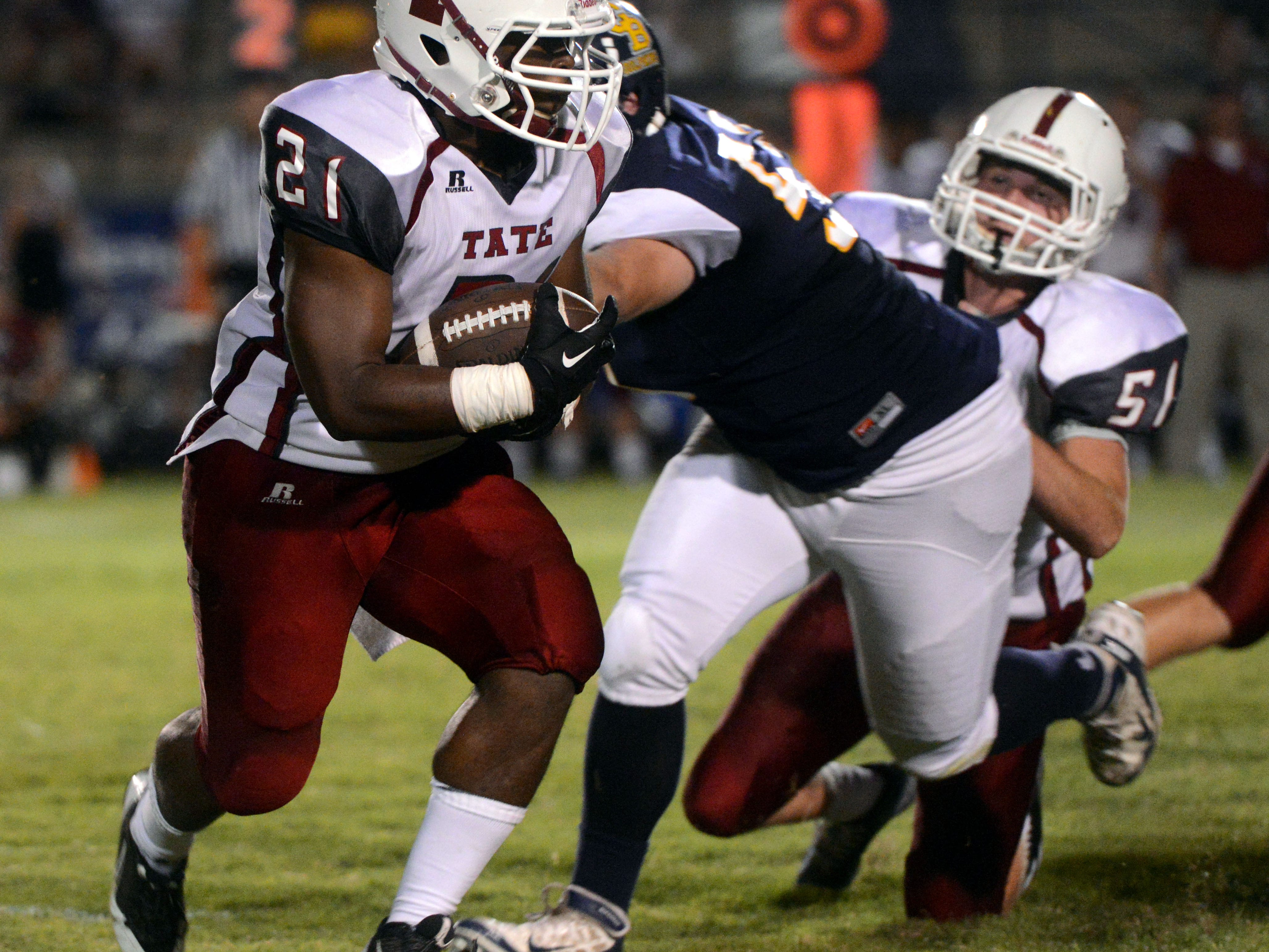 Tate High School running back LaDarius Thomas carries the ball through traffic Thursday while taking on Gulf Breeze their kickoff classic.