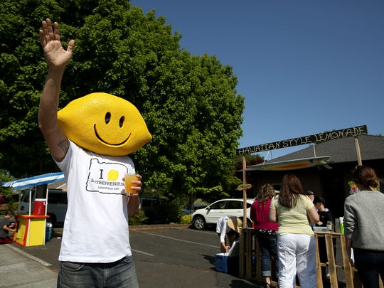 Chip Conrad, state director of Lemonade Day Oregon, waves to cars Sunday along Chemawa Road in Keizer during Lemonade Day, a program that empowers youths to start and operate their own businesses.