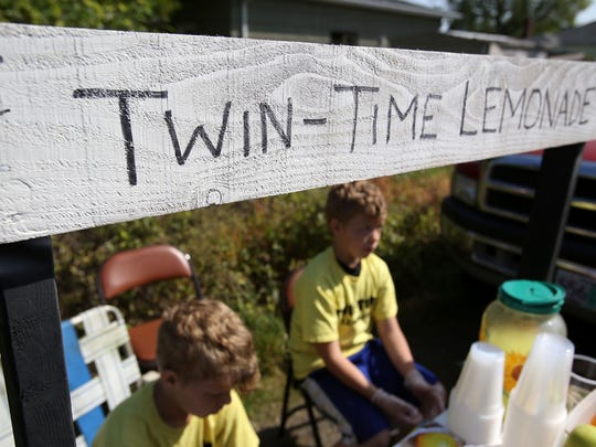 Twins Micah Rader, left, and Matthew Rader, 9, sell lemonade to visitors Sunday in Keizer during Lemonade Day Salem-Keizer. The brothers were also selling cookies, potato chips and fruit at their stand.