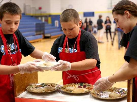 Benjamin Villalvazo, left, Hayden Walker and Hanna Kempf, all seventh-graders, plate cookies to be judged on Wednesday at Leslie Middle School in Salem.