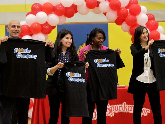 Otis Spunkmeyer executives John Yamin,left, Kristina Dermody, Charice Grace and Doris Pham accept Cookie Company T-shirts on Wednesday during a cookie contest at Leslie Middle School in Salem. Otis Spunkmeyer representatives judged the cookies created and baked by the middle school students. The winning recipe will be made into regulation company cookie dough and sent to the school for baking.