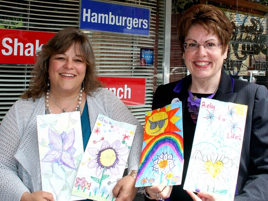 Salem Saturday Market Director Lisa Sherman and Relay for Life Event Co-Chair Kathy Ottele share bags decorated by students at Hammond Elementary at the Statesman Journal's Holding Court at the Court Street Dairy Lunch in downtown Salem on Tuesday.