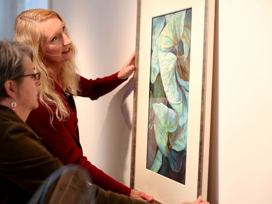Debbie Leahy (left) and Catherine Alexander hang a painting in the Compass Gallery at the Willamette Heritage Center. In the past eight months, they've founded two galleries at the center.